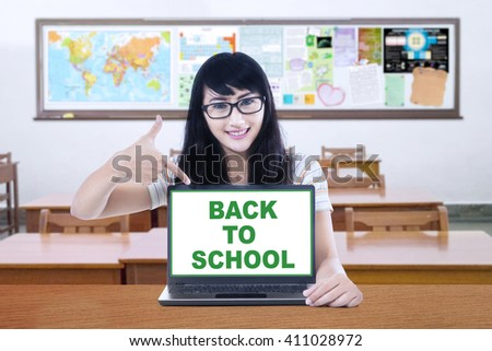 Female high school student showing a text of back to school with a laptop computer screen in the classroom - stock photo