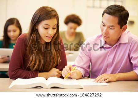 Female High School Student With Teacher Studying At Desk - stock photo