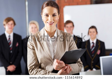 female high school teacher in classroom with group of students - stock photo