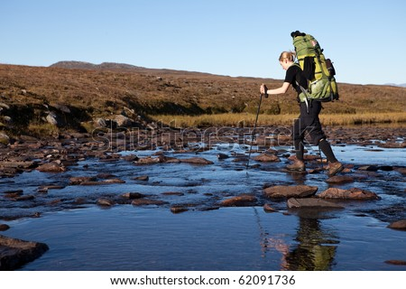 female hiker cross the river - stock photo