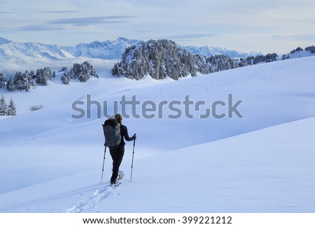 Female hiker in the snow covered mountains in France during a micro adventure. Shallow focus.