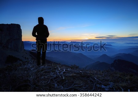 Female hiker looking at the tranquil sunset in the Vergers mountains, France.