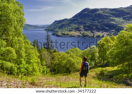 Female hiker looking at Ullswater, Lake District National Park, Cumbria, England. - stock photo