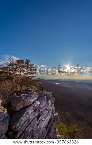 Female hiker standing at the edge of a rocky cliff on an Appalachian mountain enjoying the sun and vista - stock photo