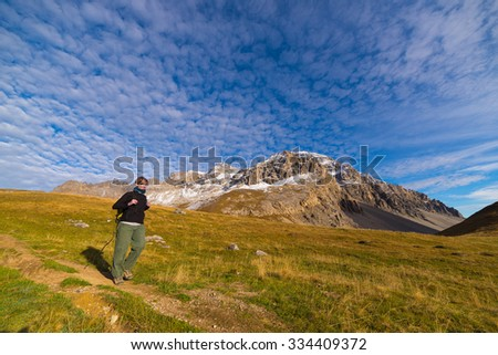 Female hiker walking on footpath in a colorful valley with scenic sky and clouds. Wide angle shot from below in the Italian French Alps. Concept of healthy lifestyle. - stock photo