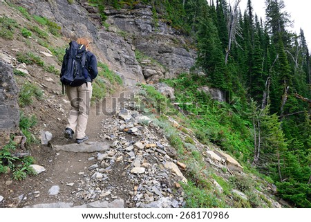 female hiker with a backpack on a highland alpine trail, view from the back - stock photo