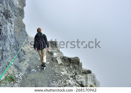 female hiker with a backpack on a steep highland alpine trail in heavy fog, view from the back - stock photo