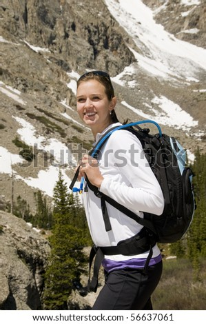 Female hiker with backpack in front of mountains