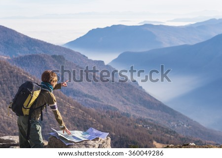 Female hiker with backpack reading trekking map while pointing finger to the mountains on the italian Alps. Mist and fog in the valley below, larch and pine tree forest around. Selective focus. - stock photo