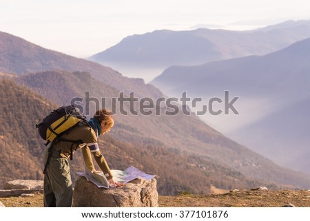 Female hiker with backpack reading trekking map while resting at panoramic mountain spot on the italian Alps. Mist in the valley below, larch tree forest around. Selective focus, warm sunset light. - stock photo