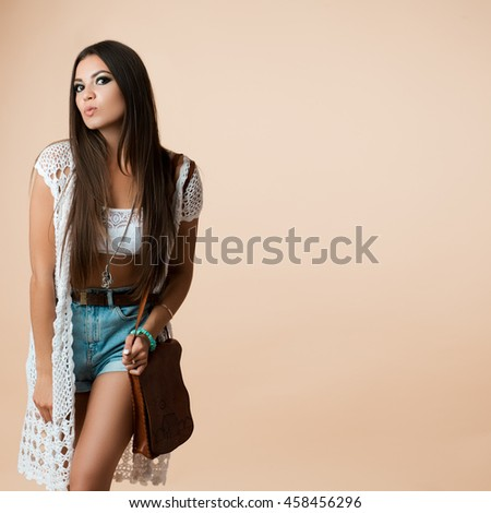 Female hipster glamour portrait of long straight hair sending a kiss. Fashion outfit, denim shorts, posing in the Studio. Place for text free