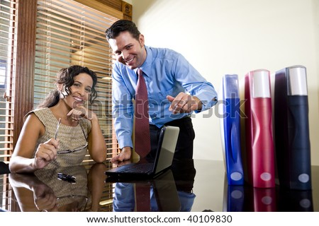 Female Hispanic office worker and male colleague in boardroom with laptop computer - stock photo
