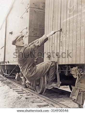Female hobo climbing freight train - stock photo