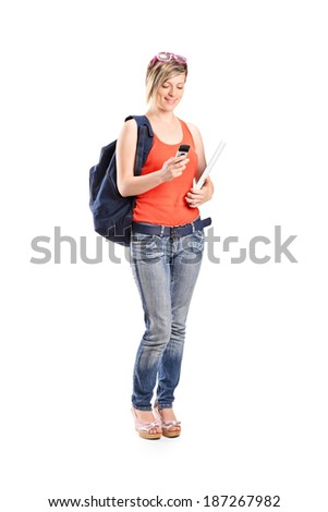 Female holding a ruler and looking at cell phone isolated on white background - stock photo