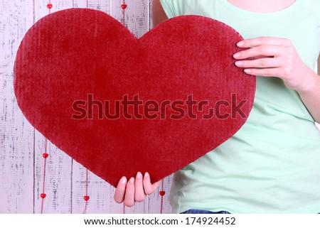 Female holding big red heart on wooden background - stock photo