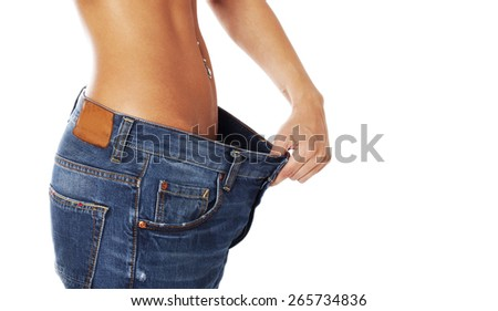 Female holding her pants open and showing how much centimeters she has already lost. Isolated on white.