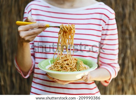 Female holding plate of spaghetti in one hand and spaghetti on fork with another - stock photo