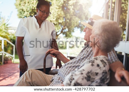 Female home caregiver looking after senior couple relaxing on a bench outside their retirement home. - stock photo