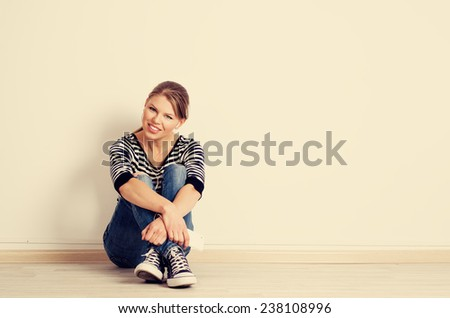 Female homeowner sitting on the floor in her new house planning interior decoration and furnish.  - stock photo