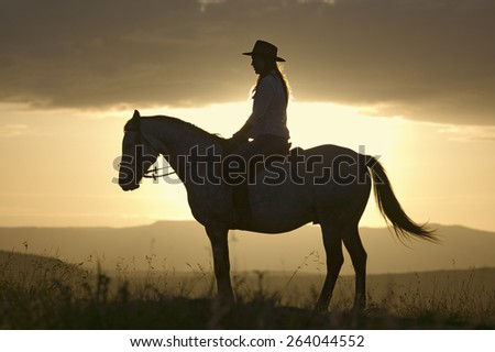 Female horseback rider and horse ride to overlook at Lewa Wildlife Conservancy in North Kenya, Africa at sunset - stock photo