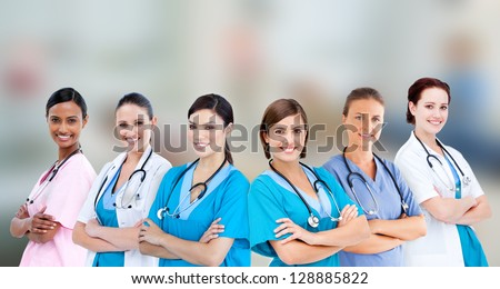 Female hospital workers standing arms folded in line on blurred background