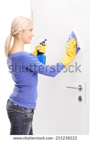 Female housekeeper cleaning a door isolated on white background - stock photo