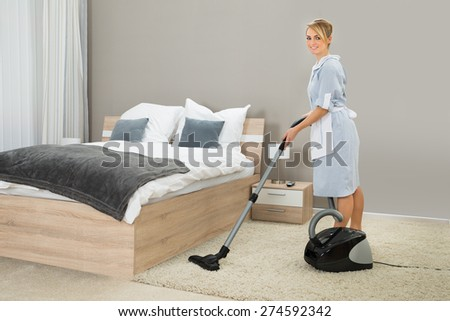 Female Housekeeper Cleaning Rug With Vacuum Cleaner In Hotel Room - stock photo