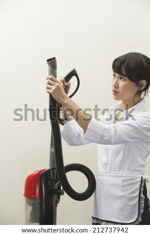 Female housekeeper holding vacuum cleaner pipe against gray background - stock photo