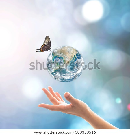 Female human hand reaching beautiful planet and butterfly with bokeh and sun flare on blurred blue sky background: Saving clean environment and climate: Elements of this image furnished by NASA   - stock photo