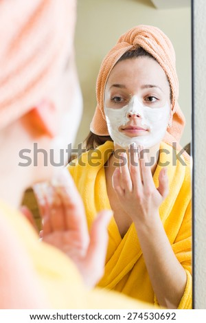 Female in bathrobe treating skin with face pack in front of the mirror  - stock photo