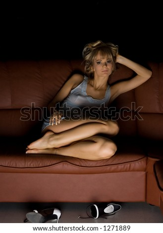 female in blue dress sitting on the sofa with her shoes off
