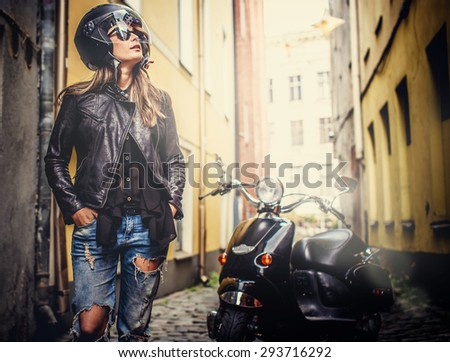 Female in blue jeans, leather jacket and motorcycle helmet standing near scooter in old town. - stock photo