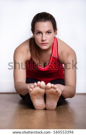 Female in her twenties sitting on a studio floor exercising and stretching. Focus on the face. - stock photo