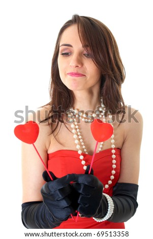 female in red dress holds two small red hearts in front of her, isolated on white background - stock photo
