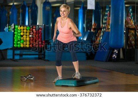 Female in step class fitness aerobic interval high intensity calorie burn pilates exercise - stock photo