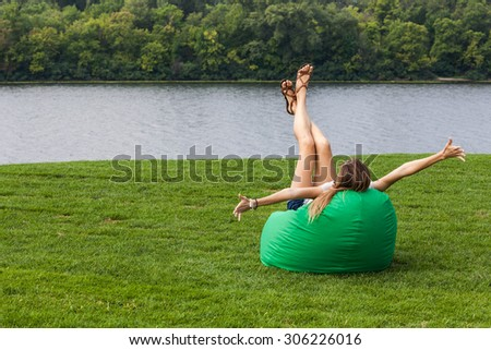 Female in the bean bag chair on the green grass, happy and excited