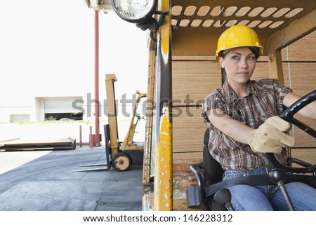 Female industrial worker driving forklift truck - stock photo