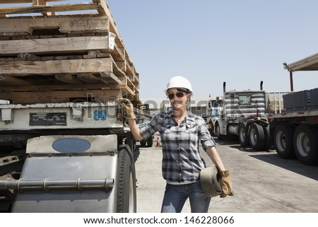 Female industrial worker standing by flatbed truck in timber yard - stock photo