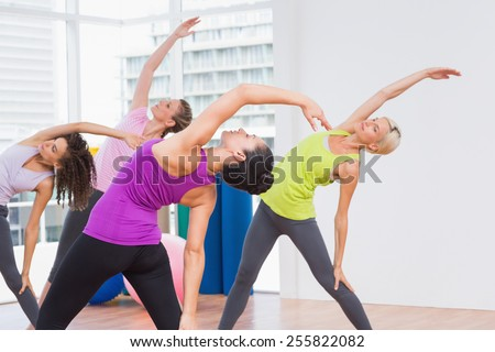 Female instructor and female friends doing stretching exercise at gym - stock photo