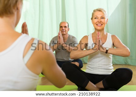 Female instructor and mature couple practicing yoga - stock photo