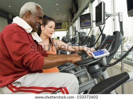 Female instructor assisting senior man on exercise bike at health club - stock photo