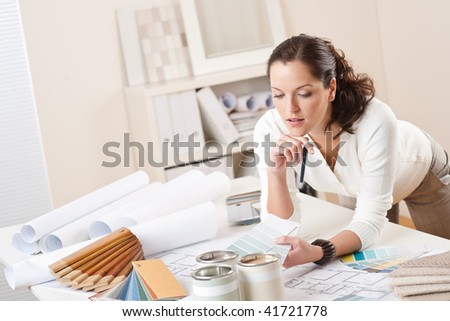 Female interior designer working at office with color swatch and paint - stock photo