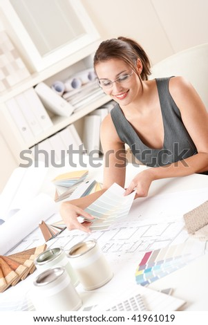 Female interior designer working at office with color swatch choosing color