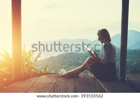 Female is typing something in diary on touch pad, while is sitting against amazing Asian landscape in beautiful summer evening. Woman is watching video on digital tablet during her trip in Thailand - stock photo