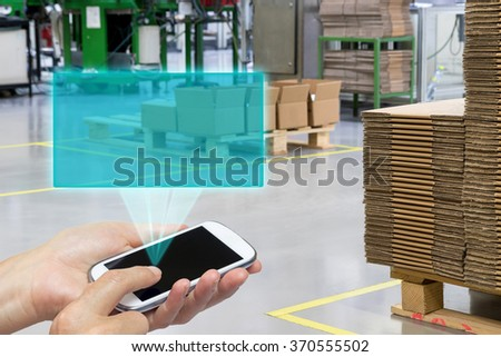 Female is using the smart phone. Blank transparent rectangle radiates from the screen smart phone. The rectangle is ready for your text. Folded cardboard boxes are in the background.  - stock photo