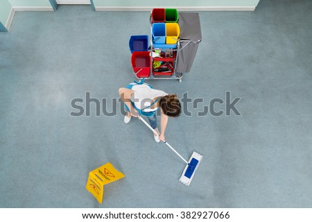 Female Janitor Mopping Floor With Caution Sign - stock photo