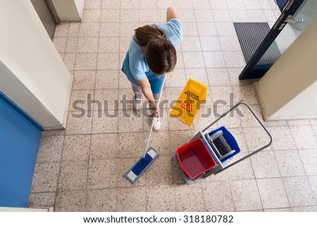 Female Janitor Mopping Floor With Cleaning Equipments And Wet Floor Sign On Floor - stock photo