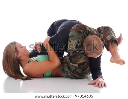Female Jiu-Jitsu instructor demonstrating an inverted triangle choke submission - stock photo