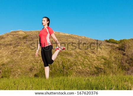 Female jogger stretching  - stock photo