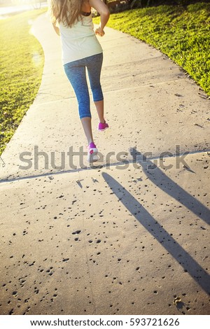 stock photo female jogging in a city park view from behind beautiful blonde woman running along a city park 593721626